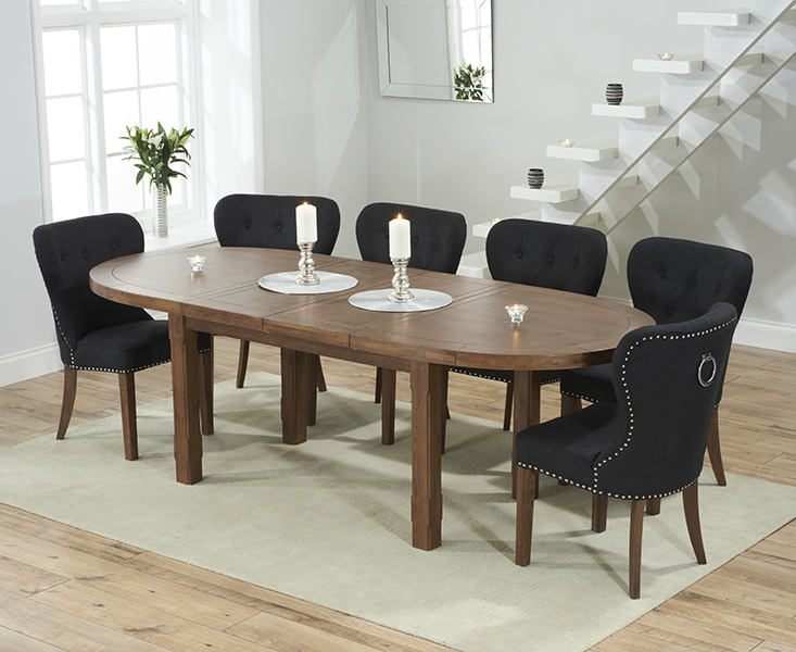 solid dark oak oval extending dining table with 6 kalim black chairs